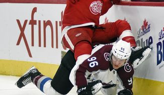Detroit Red Wings center Luke Glendening, top, falls atop of Colorado Avalanche right wing Mikko Rantanen (96), of Finland, during the first period of an NHL hockey game in Detroit, Sunday, Dec. 2, 2018. (AP Photo/Jose Juarez)