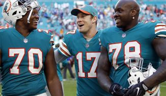 Miami Dolphins quarterback Ryan Tannehill (17) celebrates with offensive tackles Ja'Wuan James (70) and Laremy Tunsil (78) after defeating the Buffalo Bills 21-17 at an NFL football game, Sunday, Dec. 2, 2018, in Miami Gardens, Fla. (AP Photo/Joel Auerbach)