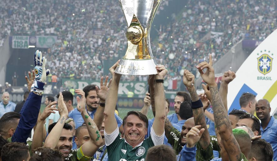 Brazil's President-elect Jair Bolsonaro holds up the Brazilian soccer championship trophy, as he celebrates with Palmeiras soccer club who won the title after defeating Vitoria, in Sao Paulo, Brazil, Sunday, Dec. 2, 2018. (AP Photo/Andre Penner)