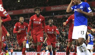 Liverpool forward Divock Origi, second from left, celebrates after scoring his side's first goal during the English Premier League soccer match between Liverpool and Everton at Anfield Stadium in Liverpool, England, Sunday, Dec. 2, 2018. (AP Photo/Jon Super)