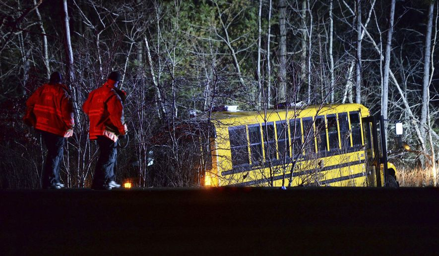 Emergency medical crew respond to a school bus that crashed into the woods off Route 24 south in Berkley, Mass., on Saturday, Dec. 1, 2018. The group was returning back to Tiverton, R.I. from LaSalette Shrine in North Attleboro, Mass. (Marc Vasconcellos/The Enterprise via AP)