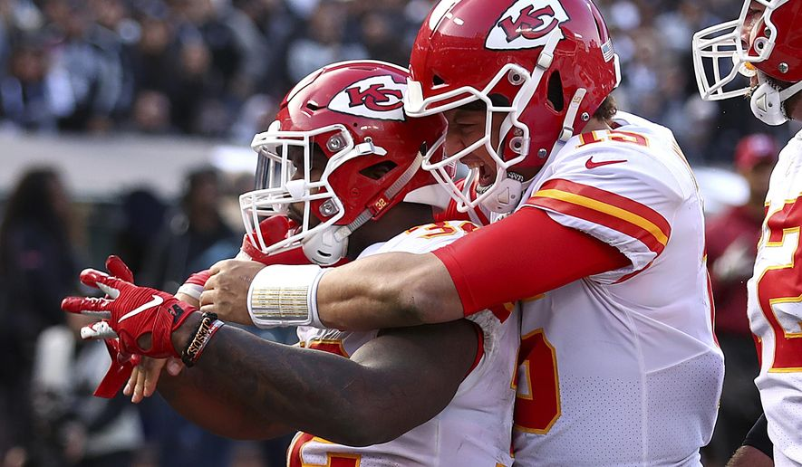 Kansas City Chiefs running back Spencer Ware, left, is congratulated by quarterback Patrick Mahomes after scoring against the Oakland Raiders during the second half of an NFL football game in Oakland, Calif., Sunday, Dec. 2, 2018. (AP Photo/Ben Margot)
