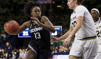 Connecticut's Christyn Williams (13) drives in next to Notre Dame's Jessica Shepard (32) during the first half of an NCAA college basketball game Sunday, Dec. 2, 2018, in South Bend, Ind. (AP Photo/Robert Franklin)