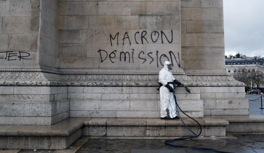 "A worker is about to clean a graffiti reading "" Macron resignation"" on the Arc de Triomphe the day after a demonstration, in Paris, Sunday, Dec. 2, 2018. A protest against rising taxes and the high cost of living turned into a riot in the French capital, as activists torched cars, smashed windows, looted stores and tagged the Arc de Triomphe with multi-colored graffiti. (AP Photo/Thibault Camus)"