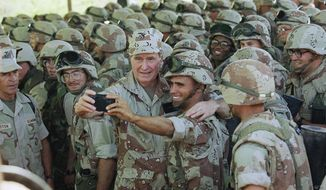 """FILE - In this Friday, Jan. 1, 1993 file photo, U.S. President George H.W. Bush holds a camera, which he borrowed from the Marine to snap the picture, for a self-portrait with Marines at the airport in Baidoa, Somalia. In the final days of his presidency, George H.W. Bush committed the U.S. military to a mission many would later regret, ordering more than 20,000 troops into Somalia to """"save thousands of innocents from death."""" (AP Photo/John Moore, File)"""