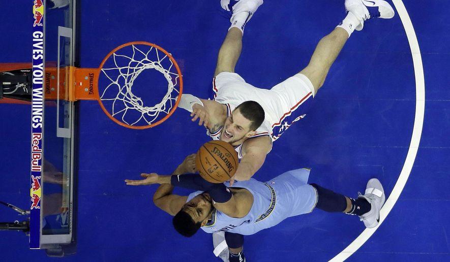 Philadelphia 76ers' Mike Muscala, top, tries to shoot past Memphis Grizzlies' Garrett Temple during the first half of an NBA basketball game, Sunday, Dec. 2, 2018, in Philadelphia. (AP Photo/Matt Slocum)
