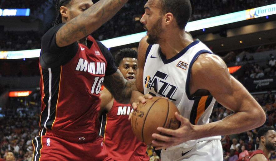 Utah Jazz center Rudy Gobert (27) dribbles to the basket past the Miami Heat defense of James Johnson (16) during the first half of an NBA basketball game, Sunday, Dec 2, 2018, in Miami. (AP Photo/Gaston De Cardenas)