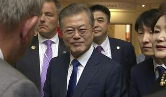 "In this image made from a video, South Korean President Moon Jae-in, center, prepares to leave after a wreath laying ceremony at the Auckland War Memorial Museum in Auckland, New Zealand Monday, Dec. 3, 2018. Moon says U.S. President Donald Trump told him he has a ""very friendly view"" of North Korean leader Kim Jong Un and wants to grant his wishes if he denuclearizes. (TVNZ via AP)"