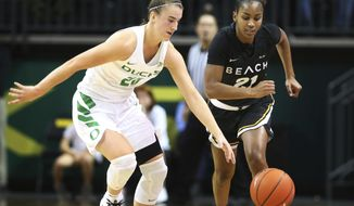 Oregon's Sabrina Ionescu, left, forces a turnover against Long Beach State's Shanaijah Davison during the second half of an NCAA college basketball game Sunday, Dec. 2, 2018, in Eugene, Ore. (Chris Pietsch/The Register-Guard via AP)