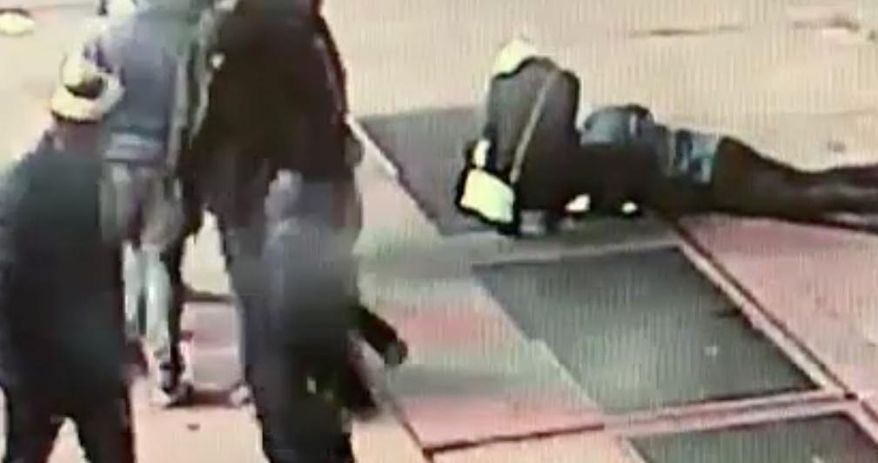 In this Nov. 30, 2018, image taken from surveillance video provided by the New York City Police Department, a man tries to see the engagement ring that he dropped down a utility grate on New York's Times Square. The New York City Police Department says the man was proposing to his girlfriend just before midnight Friday when he dropped the ring and it fell about eight feet down the utility grate. Police were initially unable to locate the ring Friday night but found it on Saturday morning. The couple did not provide their contact information but the NYPD would like to reunite them with the ring. (NYPD via AP)