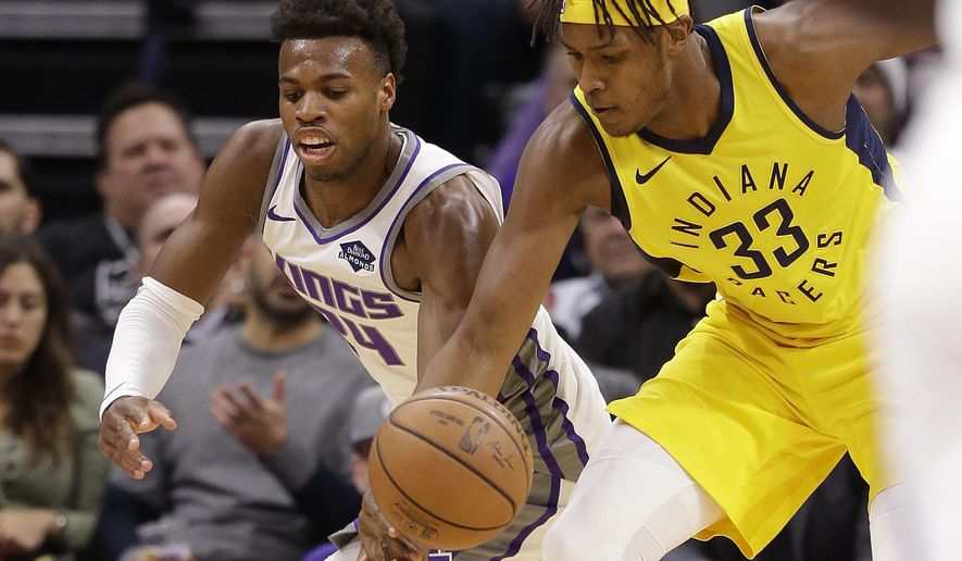 Sacramento Kings guard Buddy Hield, left, and Indiana Pacers center Myles Turner scramble for the ball during the first quarter of an NBA basketball game, Saturday, Dec. 1, 2018, in Sacramento, Calif. (AP Photo/Rich Pedroncelli)