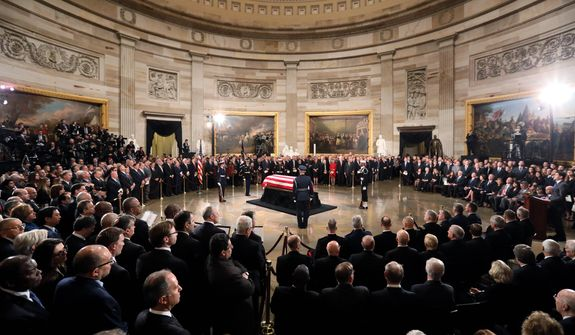 The flag-draped casket of former President George H.W. Bush lies in state in the Capitol Rotunda in Washington, Monday, Dec. 3, 2018. (Jonathan Ernst/Pool via AP)