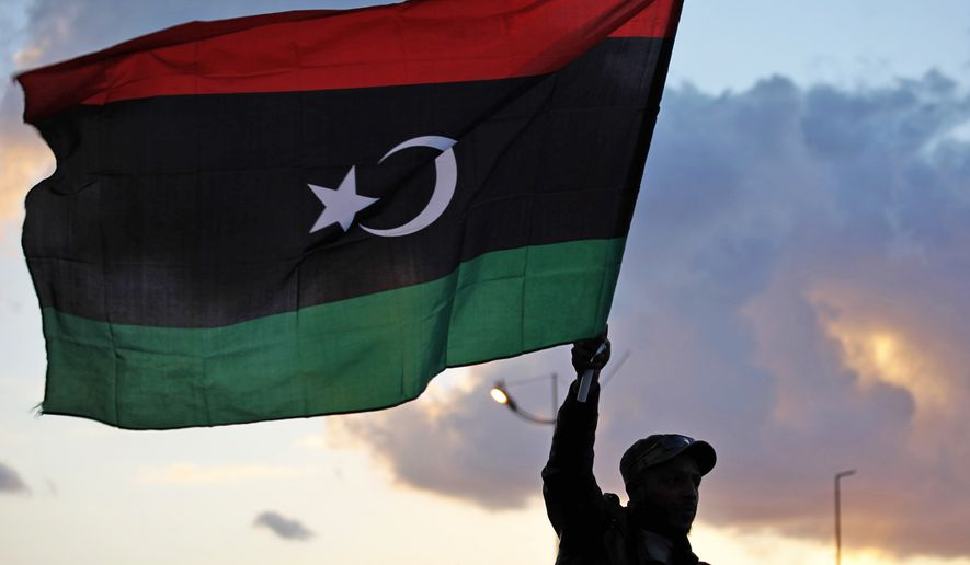 A Libyan waves the national flag during commemorations to mark the second anniversary of the revolution that ousted Moammar Gadhafi in Benghazi, Libya, Friday, Feb, 15, 2013. (AP Photo/Mohammad Hannon)