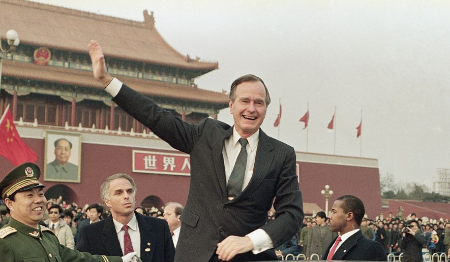 "In this Feb. 25, 1989, file photo, then U.S. President  George H.W. Bush stands on his car and waves to crowds in Tiananman Square in Beijing. Chinese state media are praising Bush as a ""statesman of vision,"" recalling the late president's role in helping end the Cold War and establishing policies toward China. The China Daily newspaper said Monday, Dec. 3, 2018, that Bush in the 1980s realized China was different from the Soviet Union and recognized the potential for cooperation. (AP Photo/Doug Mills, File)"