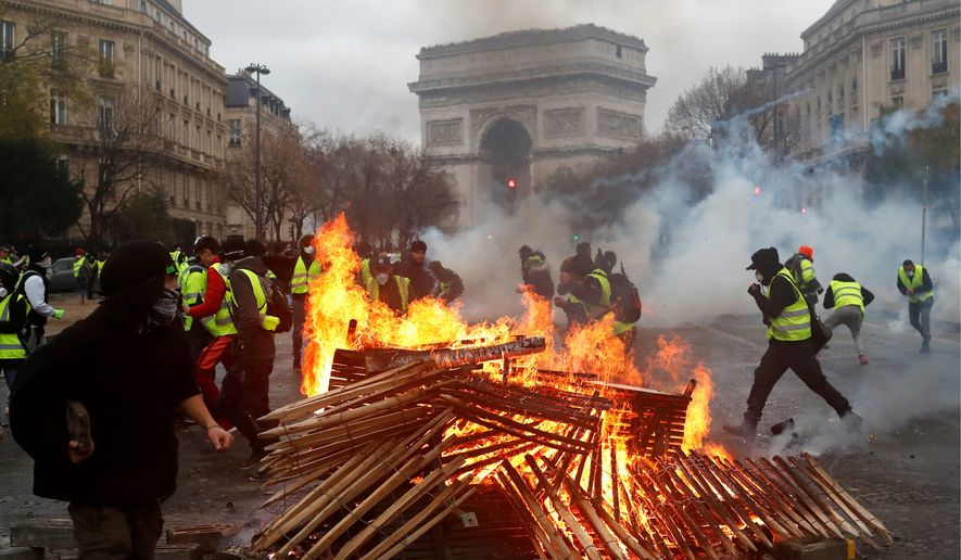 Demonstrators run by a burning fire near the Arc de Triomphe during a demonstration Saturday, Dec.1, 2018 in Paris. Paris police say at least 63 people have been arrested in violent clashes between protesters and police amid nationwide demonstrations against rising taxes and President Emmanuel Macron's policies. (AP Photo/Thibault Camus)