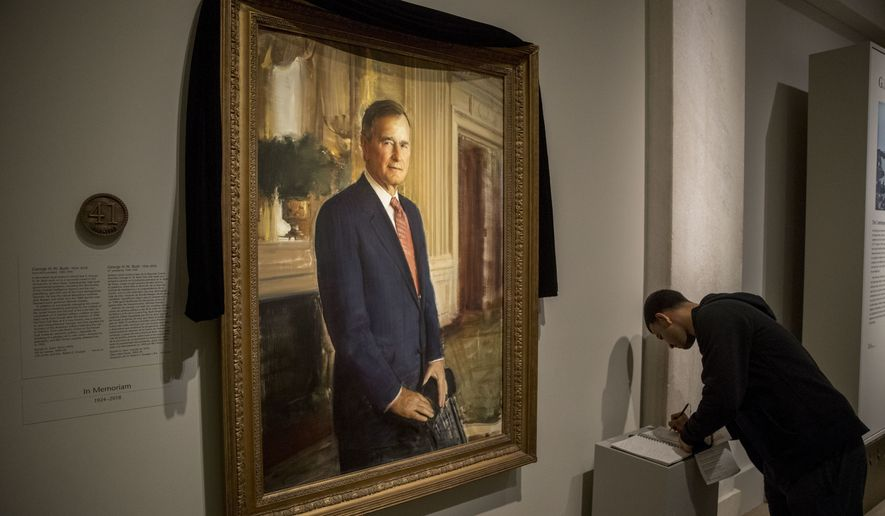 Ameer Hassan of New York stops to sign the condolence book as the official portrait of former President George H.W. Bush is draped in black cloth at the National Portrait Gallery in Washington, Monday, Dec. 3, 2018, to mark his passing. Bush will lay in state at the Capitol building this week before being buried in Texas. (AP Photo/Andrew Harnik)