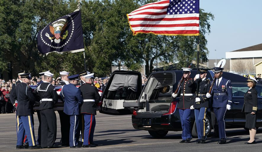 The flag-draped casket of former President George H.W. Bush is carried by a joint services military honor guard to Special Air Mission 41 at Ellington Field during a departure ceremony Monday, Dec. 3, 2018, in Houston. (AP Photo/David J. Phillip, Pool)