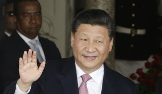 Chinese President Xi Jinping waves to reporters as he arrives at the presidential for a meeting with Panama's president, in Panama City, Monday, Dec. 3, 2018. Xi Jinping is in Panama for his first trip since Panama cut ties with Taiwan in favor of resuming or establishing relations with China. (AP Photo/Arnulfo Franco) ** FILE **