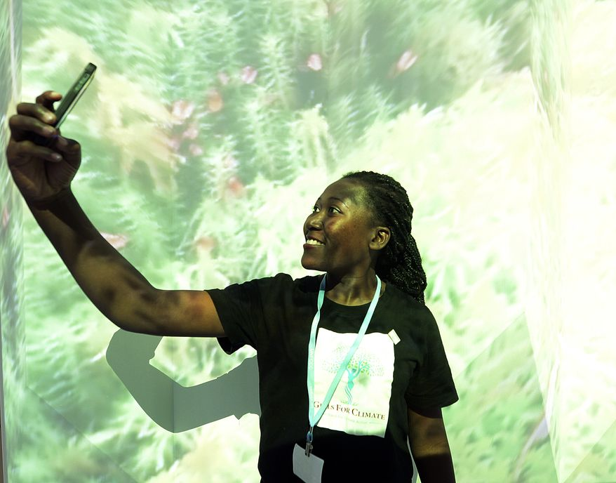 A visitor to the U.N. climate conference takes a selfie at an exhibition about forests and global warming, in Katowice, Poland, Monday, Dec. 3, 2018. The COP24 UN Climate Change Conference is taking place in Katowice, Poland. Negotiators from around the world are meeting for talks on curbing climate change. (AP Photo/Czarek Sokolowski)