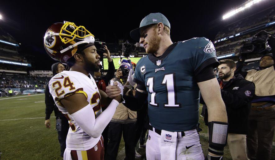 Washington Redskins' Josh Norman and Philadelphia Eagles' Carson Wentz meet after an NFL football game, Monday, Dec. 3, 2018, in Philadelphia. Philadelphia won 28-13. (AP Photo/Matt Rourke)