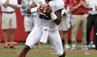 FILE - In this Oct. 6, 2018, file photo, Alabama quarterback Tua Tagovailoa rolls out before throwing a touchdown pass on the first play of the game against Arkansas in the first half of an NCAA college football game, in Fayetteville, Ark. Tagovailoa is the offensive player of the year and one of five members of the top-ranked Crimson Tide to earn first-team honors on The Associated Press All-Southeastern Conference team, announced Monday, Dec. 3, 2018. Tagovailoa, one of the prime contenders for the Heisman Trophy, has thrown 37 touchdown passes with only four interceptions to rank second nationally in passing efficiency. (AP Photo/Michael Woods, File)