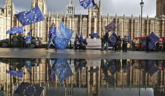 Protesters are reflected in a puddle as they wave European flags to demonstrate against Brexit in front of the Parliament in London, Monday, Dec. 3, 2018. (AP Photo/Frank Augstein)