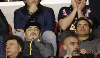 Dorados head coach Diego Maradona, left center, watches the final leg of Mexico's second division soccer league against Atletico San Luis, in San Luis Potosi, Mexico, Sunday, Dec. 2, 2018. Atletico San Luis beat Dorados 4-2 in the match, giving the aggregate series a 4-3 and is the champion of the second division. (AP Photo/Eduardo Verdugo)