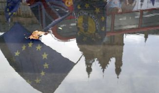 Protesters are reflected in a puddle as they wave European flags to demonstrate against Brexit in front of the Parliament in London, Monday, Dec. 3, 2018. British Prime Minister Theresa May is battling to persuade lawmakers to support the divorce agreement between Britain and the European Union in a Dec. 11 House of Commons vote. Opposition parties say they will vote against it, as do dozens of lawmakers from May's Conservatives. (AP Photo/Frank Augstein)