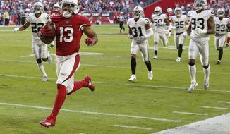 FILE - In this Nov. 18, 2018, file photo, Arizona Cardinals wide receiver Christian Kirk (13) runs for a touchdown after a catch against the Oakland Raiders during the first half of an NFL football game in Glendale, Ariz. Kirk broke a foot in a game Sunday, Dec. 2, 2018, at Green Bay and is out for the season. (AP Photo/Ross D. Franklin, File)