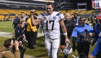 Photographers surround Los Angeles Chargers quarterback Philip Rivers (17) as he leaves the field after defeating the Pittsburgh Steelers 33-30 in an NFL football game, Sunday, Dec. 2, 2018, in Pittsburgh. (AP Photo/Don Wright)
