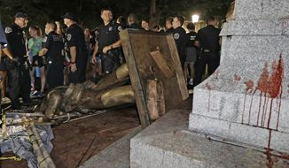 In this Aug. 20, 2018, file photo, police stand guard after the confederate statue known as Silent Sam was toppled by protesters on campus at the University of North Carolina in Chapel Hill, N.C. (AP Photo/Gerry Broome, File)