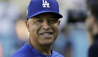 "FILE - In this Oct. 27, 2018, file photo, Los Angeles Dodgers manager Dave Roberts watches batting practice before Game 4 of the World Series baseball game against the Boston Red Sox, in Los Angeles. The Dodgers have agreed on a four-year contract with manager Dave Roberts, which would keep him at the helm of the team through 2022. ""Keeping Doc as our leader on the field was a top priority this offseason and now that we've accomplished that we are excited to collectively shift all of our focus to doing all we can to bring a World Championship to our passionate fans,"" Andrew Friedman, the Dodgers president of baseball operations, said in a statement Monday, Dec. 3, 2018. (AP Photo/David J. Phillip, File)"
