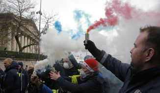 Ambulance workers hold flares outside the National Assembly in Paris, Monday, Dec. 3, 2018. Ambulance workers took to the streets and gathered close to the National Assembly in downtown Paris to complain about changes to working conditions as French Prime Minister Edouard Philippe is holding crisis talks with representatives of major political parties in the wake of violent anti-government protests that have rocked Paris. (AP Photo/Michel Euler)