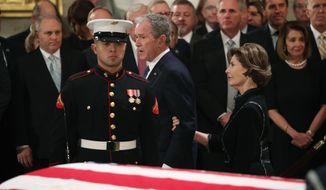 Former President George W. Bush, with his wife former first lady Laura, walks past the casket of his father, former President George H.W. Bush at the Capitol in Washington, Monday, Dec. 3, 2018. (Jonathan Ernst/Pool Photo via AP)
