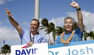 FILE - In this Nov. 6, 2018, file photo, Hawaii state Sen. Josh Green, left, candidate for lieutenant governor, and Hawaii Gov. David Ige wave to motorists in Honolulu. Ige is expected to be inaugurated to a second term leading Hawaii on Monday, Dec. 3, 2018. He will face tough challenges in the next four years, including addressing the state's chronic housing shortage and teacher shortage. He has also vowed to boost local food production and renewable energy. Joining him will be the state's newly elected lieutenant governor, Green, an emergency room doctor and state senator from the Big Island. (AP Photo/Marco Garcia, File)