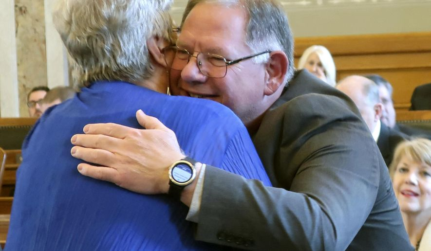 Kansas state Rep. Dan Hawkins, R-Wichita, right, gets a hug from Rep. Brenda Landwehr, also R-Wichita, left, after being chosen by Republicans as House majority leader, Monday, Dec. 3, 2018, at the Statehouse in Topeka, Kan. Hawkins is a conservative and has unseated moderate Majority Leader Don Hineman, R-Dighton. (AP Photo/John Hanna)