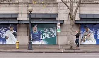 In this photo taken Thursday, Nov. 29, 2018, oversized photos of Seattle Mariners recently-traded players pitcher James Paxton, left, catcher Mike Zunino, and closer Edwin Diaz stand along a sidewalk at the team's ballpark, in Seattle. Paxton was traded to the New York Yankees and Zunino to the Tampa Bay Rays in November and Diaz was traded to the New York Mets in a deal announced Monday, Dec. 3, 2018. (AP Photo/Elaine Thompson)