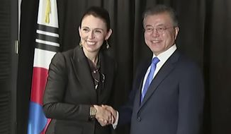 In this image made from a video, New Zealand's Prime Minister Jacinda Ardern, left, and South Korean President Moon Jae-in  shake hands in Auckland, New Zealand Tuesday, Dec. 4, 2018. Ardern says New Zealand will soon allow smoother immigration procedures for visitors from South Korea and plans to improve pension portability between the two countries. (NZ POOL via AP)