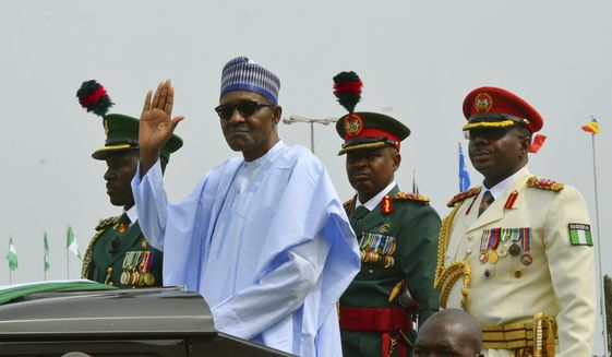 FILE - In this Monday Oct. 1, 2018 file photo, Nigerian President Muhammadu Buhari waves to the crowd during the 58th anniversary celebrations of Nigerian independence, in Abuja, Nigeria. Nigeria's president on Sunday Dec. 2, 2018, took the extraordinary step of denying rumors that he died and was replaced by a body double, telling the country that he is alive and well. (AP Photo/Olamikan Gbemiga, File)