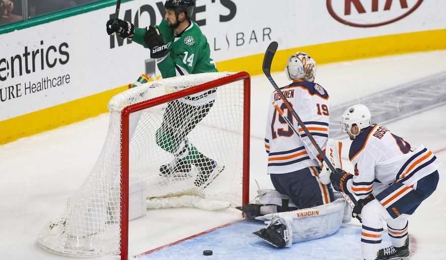 Dallas Stars left wing Jamie Benn (14) raises his stick after scoring a goal as Edmonton Oilers goaltender Mikko Koskinen (19) and defenseman Kris Russell (4) look on during the third period of an NHL hockey game Monday, Dec. 3, 2018, in Dallas. (AP Photo/Ray Carlin)