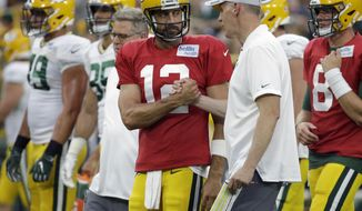 FILE - In this Aug. 4, 2018, file photo, Green Bay Packers quarterback Aaron Rodgers shakes hands with new offensive coordinator Joe Philbin during the NFL football team's Family Night practice in Green Bay, Wis. The Packers fired coach Mike McCarthy Sunday, Dec. 2, 2018, and made offensive coordinator Joe Philbin the interim head coach. (AP Photo/Mike Roemer, File)