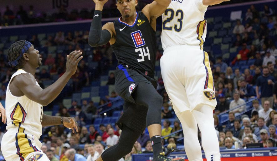 Los Angeles Clippers forward Tobias Harris (34) passes around New Orleans Pelicans forward Anthony Davis (23) and guard Jrue Holiday (11) in the first half of an NBA basketball game in New Orleans, La. Monday, Dec. 3, 2018. (AP Photo/Matthew Hinton)