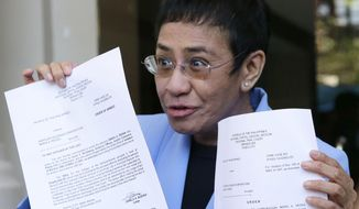 Maria Ressa, CEO of Rappler, an online news service, who has been critical of the government of Philippine President Rodrigo Duterte, shows documents after posting bail at the Pasig Regional Trial Court in metropolitan Manila, Philippines, Monday, Dec. 3, 2018. Ressa along with Rappler has been sued for tax evasion. She has declared her innocence and been freed on bail after reporting herself for arrest. (AP Photo/Aaron Favila)