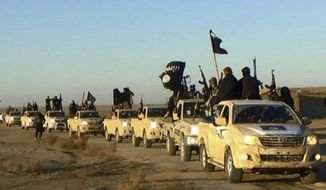 In this undated file photo released online in the summer of 2014 on a militant social media account, which has been verified and is consistent with other AP reporting, militants of the Islamic State group hold up their weapons and wave its flags on their vehicles in a convoy on a road leading to Iraq, in Raqqa, Syria. (Militant photo via AP) **FILE**