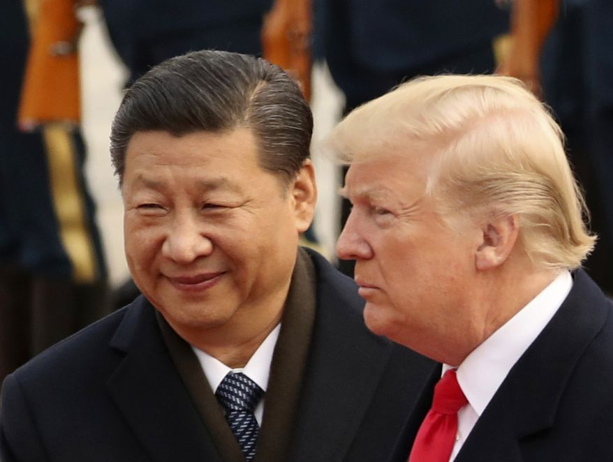 In this Nov. 9, 2017, file photo, U.S. President Donald Trump and Chinese President Xi Jinping participate in a welcome ceremony at the Great Hall of the People in Beijing, China. (AP Photo/Andrew Harnik, File)