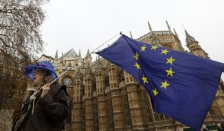An anti-Brexit campaigner waves a European Union flag in Westminster in London, Tuesday, Dec. 4, 2018. Britain's Prime Minister Theresa May is due to address Parliament Tuesday, opening five days of debate before a Dec. 11 vote on the divorce agreement.(AP Photo/Kirsty Wigglesworth)