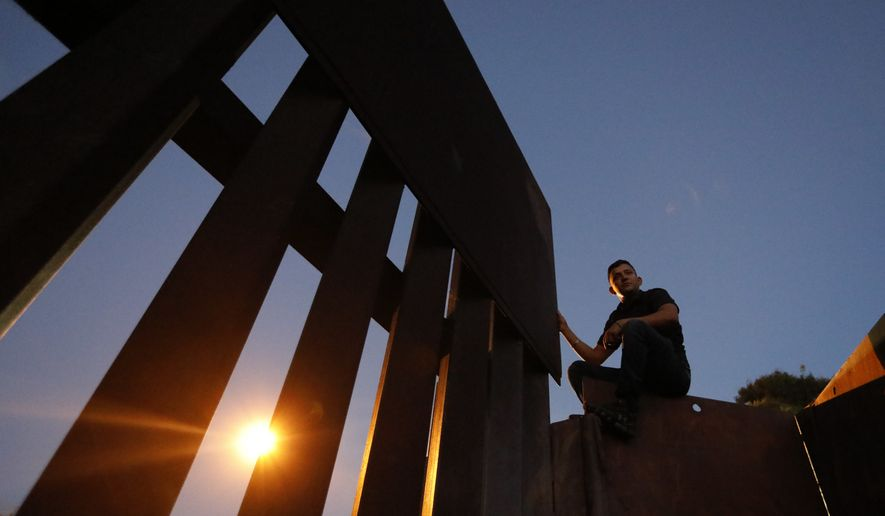 A man sits atop the U.S. border wall as he prepares to help other migrants climb over to San Ysidro, Calif., in order to surrender to the U.S. Border Patrol, in Playas de Tijuana, Mexico, Monday, Dec. 3, 2018. Thousands of Central American migrants who traveled with recent caravans want to seek asylum in the U.S. but face a decision between crossing illegally or waiting months, because the U.S. government only processes a limited number of those cases a day at the San Ysidro border crossing. (AP Photo/Rebecca Blackwell)