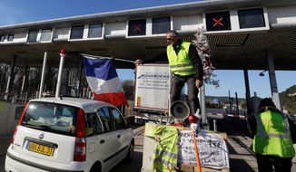 A demonstrator wearing a yellow vest waves a French flag as protesters open the toll gates on a motorway near Aix-en-Provence, southeastern France, Tuesday, Dec. 4, 2018. French Prime Minister Edouard Philippe announced a suspension of fuel tax hikes Tuesday, a major U-turn in an effort to appease a protest movement that has radicalized and plunged Paris into chaos last weekend. (AP Photo/Claude Paris)