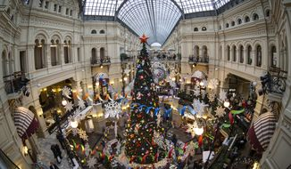 Customers walk past Christmas trees decorated for New Year celebrations. (AP Photo/Alexander Zemlianichenko)