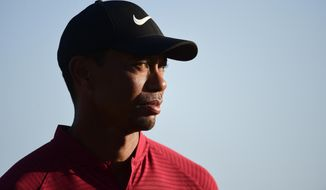 U.S. golfer Tiger Woods stands near the Hero World Challenge trophy before presenting it to Spain's Jon Rahm at Albany Golf Club in Nassau, Bahamas, Sunday, Dec. 2, 2018. (AP Photo/Dante Carrer)